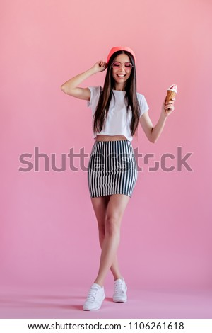 Young asian teenage girl on pink background. Stylish young woman with ice cream isolated.
