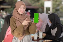 Young Asian teenager girl showing and pointing blank green phone screen while friends sitting in background on cafe or eatery