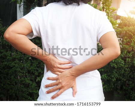 Young Asian Thai women with body aches suffering muscle injury with waist pain and back pain use hand touching and massage on body to relieve ache.