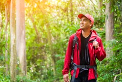 Young asian travel handsome man hiking in forest and mountain enjoy walking in nature outdoors. Image of lifestyle camping,travel,hiking or recreation concept with copy space.