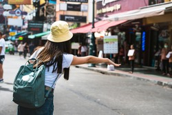 Young asian traveler happy woman in white shirt with backpack from behind view. Flag down a taxi for tourism. Khaosan road background. Bangkok City, Thailand