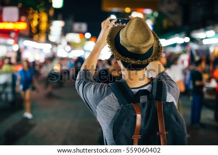 Shutterstock Young Asian traveler taking photo with mobile phone in Khaosan road at night in Bangkok, Thailand