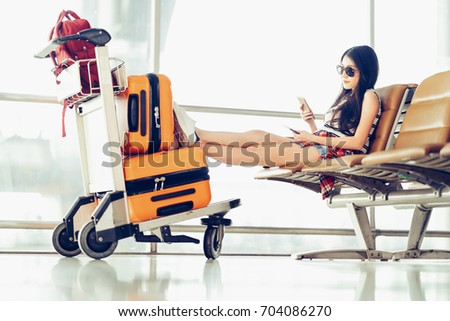 Shutterstock Young Asian traveler woman, university student sit using smartphone at airport, luggage and bag on trolley cart. Online check in mobile app, study abroad, or international tourism lifestyle concept