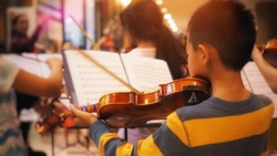 Young Asian violinist playing with orchestra band. (Selected focus)