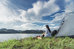 Young asian woman active camping and using laptop in stunning mountain wilderness near the lake.