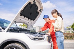 Young asian woman and mechanic opening bonnet of car. Road service. Roadside assistance.