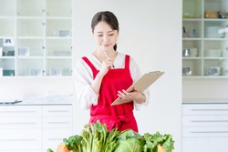 Young asian woman and vegetables. Food coordinator. Nutritionist.