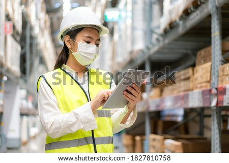 Young asian woman auditor or trainee staff wears mask working during the COVID pandemic in store warehouse shipping industrial. looking up and checks the number of items store by digital tablet. Foto stock ©