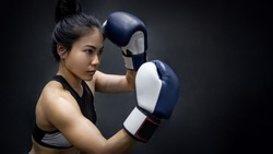 Young Asian woman boxer posing uppercut with blue boxing gloves in fitness gym. Female boxing class. Martial arts concepts