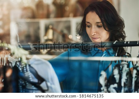 Young Asian woman browsing racks of clothing inside of a trendy boutique while out shopping Stock photo ©
