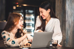 young asian woman Business people Working discuss finding new strategy solution.People discussion business plan using laptop at cafe.