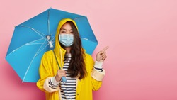 Young Asian woman caught virus during wet autumn day, wears medical mask not to spread infection points fore finger on blank space right poses under umbrella protects herself from being caught in rain