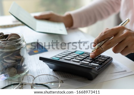 Young asian woman checking bills, taxes, bank account balance and calculating credit card expenses. Family expenses concept.