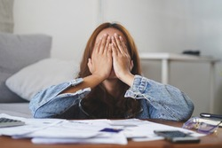 young asian woman cover her face after stressed with monthly bill expenses and credit card debt.