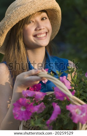 Young Asian woman cutting flowers in her garden