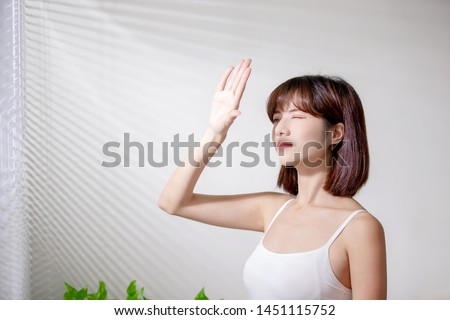 Young asian woman dislike the sunshine because afraid of suntan and oily skin #1451115752