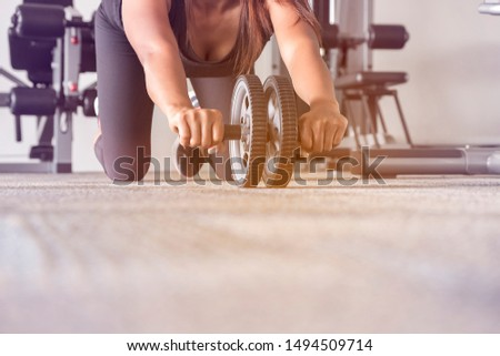 Young asian woman doing exercises in the gym with Roller slide, Freedom Beautiful Indian lady exercising building muscles and fitness woman. Fitness - concept of healthy lifestyle.