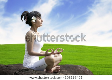 Young asian woman doing yoga exercise on a stone