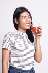 Young Asian woman drink tomato juice on white background