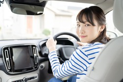 Young asian woman driving a car.