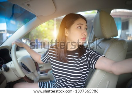 Young Asian woman driving car keeps wheel turning around looking back over shoulder check behind going reverse. Japanese girl new driver parking car. ride car backward exam vehicle concept. Foto d'archivio ©
