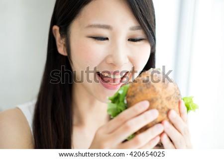 Young Asian woman eating hamburger #420654025
