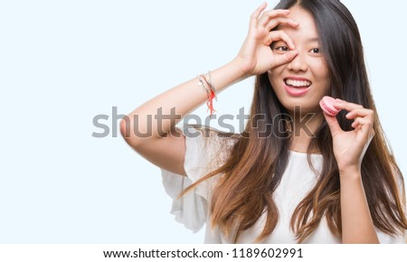 Young asian woman eating pink macaron sweet over isolated background with happy face smiling doing ok sign with hand on eye looking through fingers #1189602991