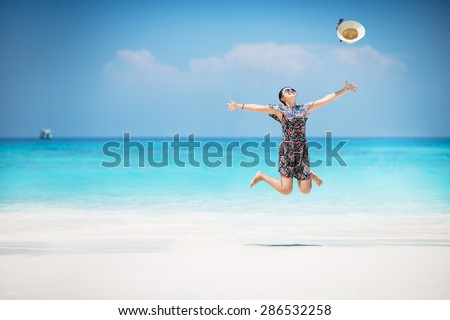 Young Asian woman enjoy on a beach, Happy holidays vacation outdoors. Jumping. #286532258