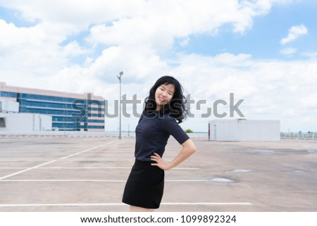 Young asian Woman enjoying face, standing on Urban Rooftop Carpark in a city and beautiful blue sky clouds view background.
