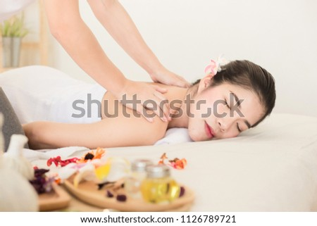Young asian woman enjoying relaxing back massage in spa. Body care, skin care, wellness, alternative medicine and relaxation Concept. #1126789721