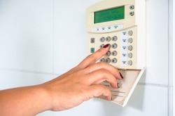 Young Asian woman entering authorization code pin on home alarm keypad. Home security concept