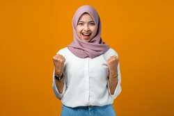 Young asian woman feeling excited and happy on yellow background
