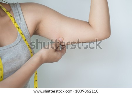 Young Asian woman feeling worried about her over weight problem and measuring her upper arm size by measuring tape. #1039862110