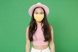 Young asian woman girl in casual pink clothes hat yellow face mask isolated on green wall background studio. Epidemic pandemic coronavirus 2019-ncov sars covid-19 flu virus concept. Looking camera