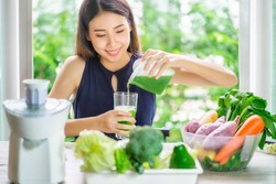 Young Asian Woman Happy Drinking Fresh Green Detox Vegetable Juice. Healthy detox vegan diet with vegetable cold pressed extractor to extract nutrients for smoothie drink. Green healthy food concept.