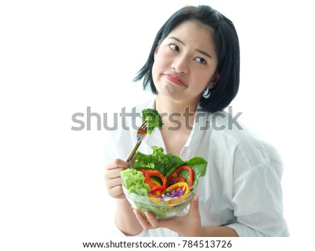 Young Asian woman hating salad vegetable on white background