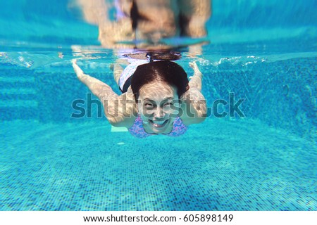 Young asian woman having fun underwater in swimming pool. #605898149