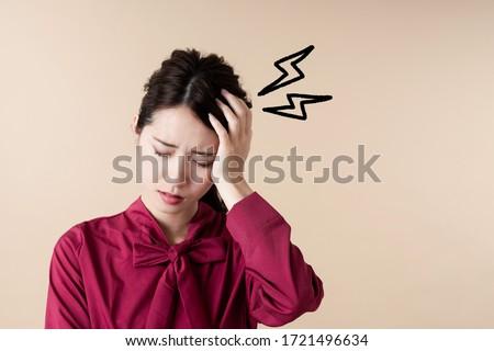 Young asian woman having head ache. Stock photo ©