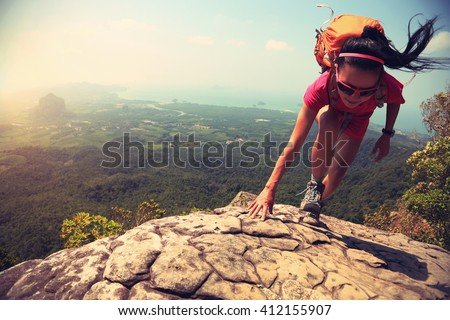 Shutterstock young asian woman hiker climbing rock on mountain peak cliff