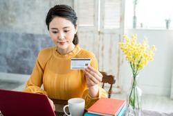 Young asian woman holding a credit card.