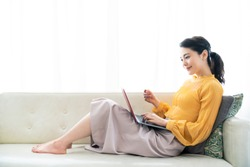 Young asian woman holding a credit card and a laptop.