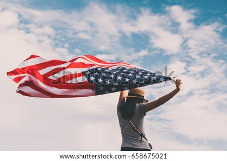 Young asian woman holding American flag on blue sky background