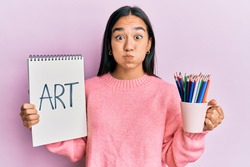 Young asian woman holding art notebook and colored pencils puffing cheeks with funny face. mouth inflated with air, catching air.