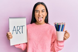 Young asian woman holding art notebook and colored pencils sticking tongue out happy with funny expression.