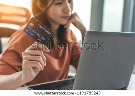 Young asian woman holding credit card and use laptop for purchase product on internet in home office, Cyber Monday shopping online concept.