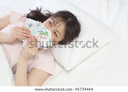 Young Asian woman holding Euro on the bed