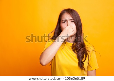 Young Asian woman  holding her nose because of a bad smell in yellow dress on yellow background