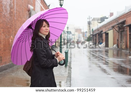Young Asian woman holding up her umbrella