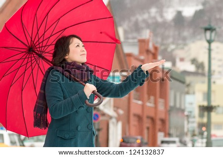 Young Asian woman holding up her umbrella in winter city