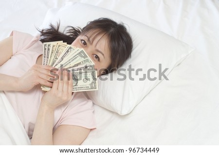 Young Asian woman holding US Dollars on the bed